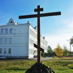 Крест на месте разрушенной церкви Василия Великого (на заднем плане - здание, где располагалось духовное училище)